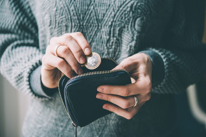 Hands putting coin in purse