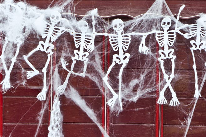 Paper skeletons decoration with fake spider webs hung on wall for Halloween party