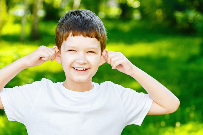 Boy holding ears to listen outdoors
