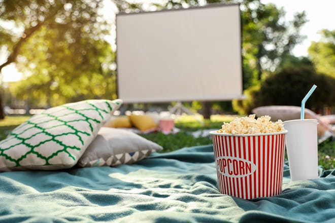 projector screen, cushions, blanket and popcorn in the garden