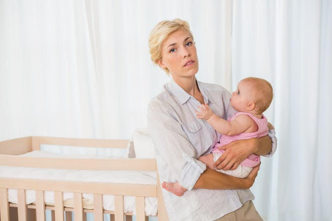 Mum holding baby next to cot