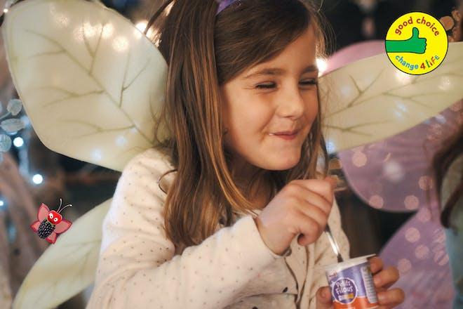 Girl dressed as fairy eating Petitis Filous