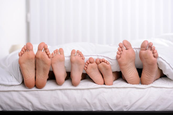 Family feet in bed