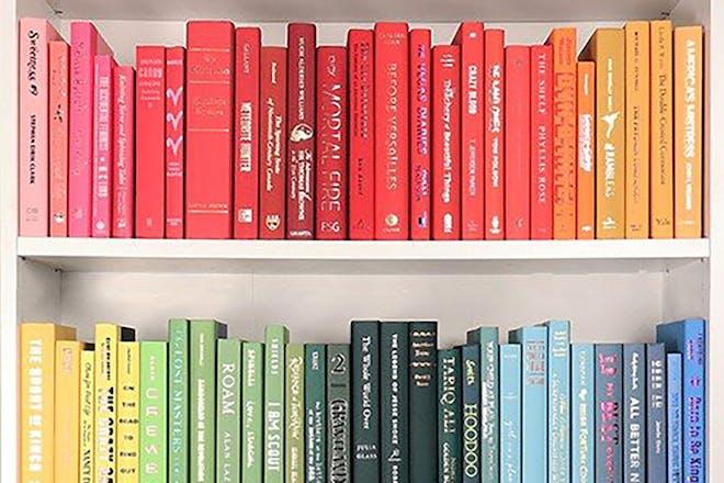 Books arranged on shelves by colour