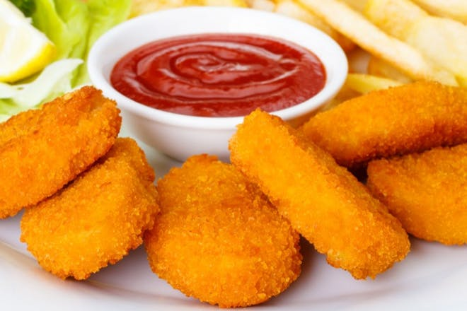A plate of chicken nuggets with ketchup