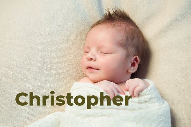 Sleeping baby wrapped in blanket and smiling. Name Christopher written in text