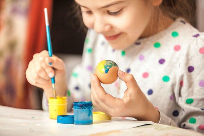Girl decorating an egg