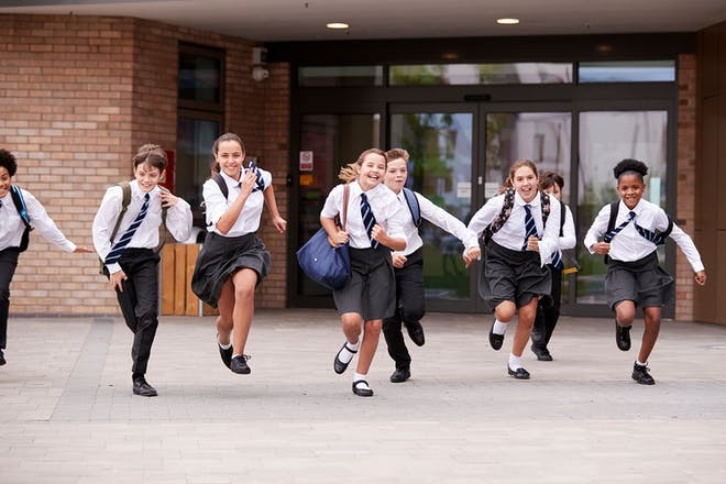 Group of laughing kids running in school playground