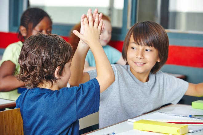 two boys giving high fives in class