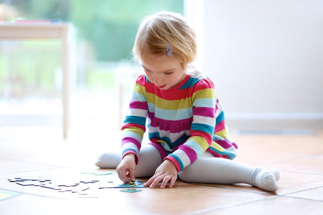 little girl in w position doing puzzle