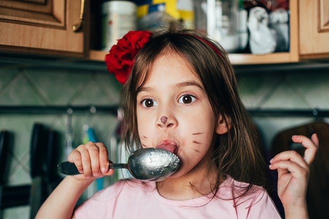 Young girl wearing cat face paint licking honey from spoon