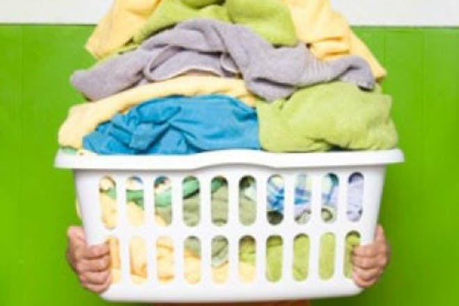 woman holding pile of washing on green background