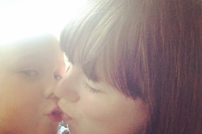 Puzzled mummy kissing son on the lips