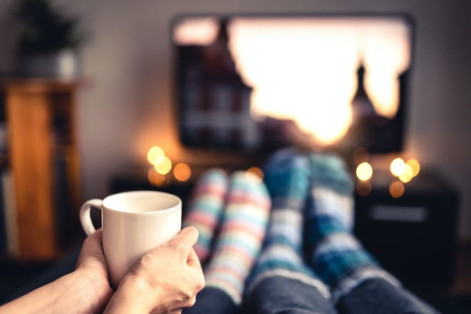 Two people watching a film with a hot drink
