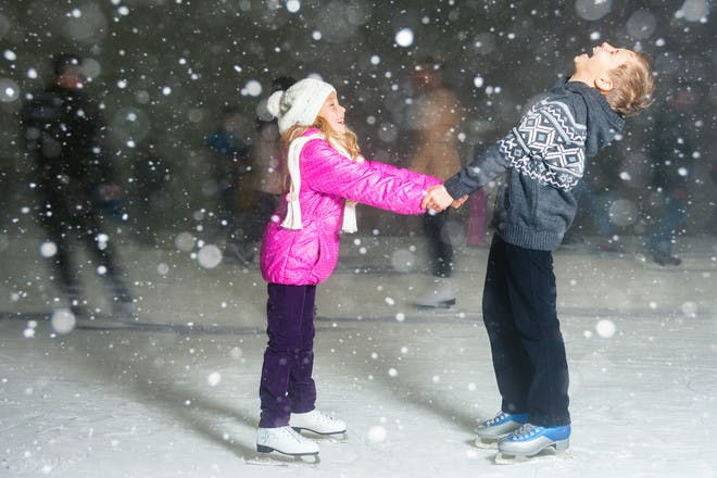 two children ice skating and laughing