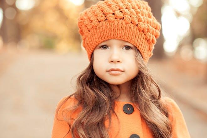 little girl wearing orange wooly hat
