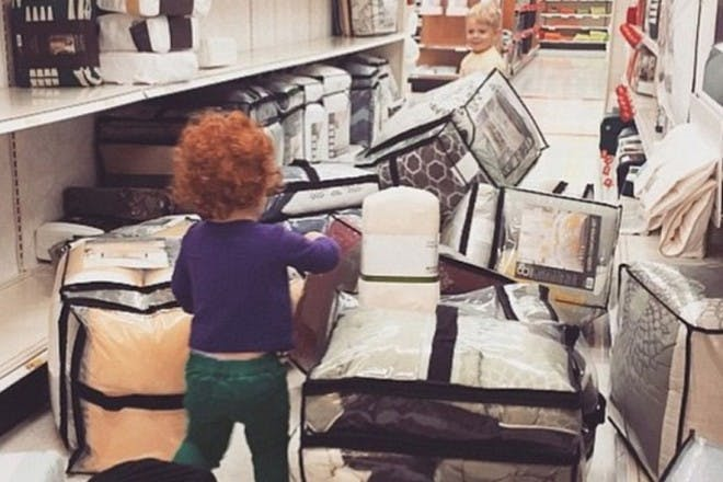 children in a shop pulling everything off shelves
