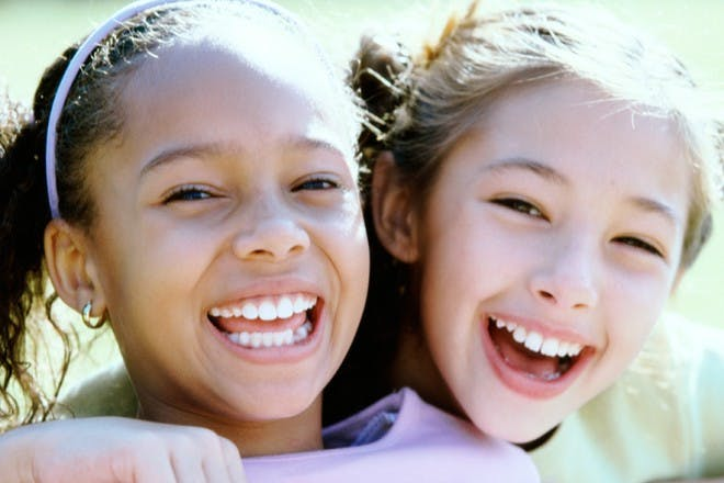 two girls hugging and laughing