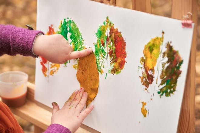 child painting with leaves