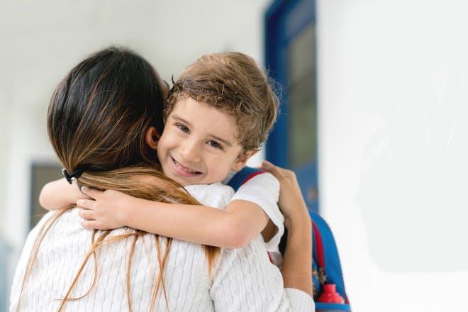 smiling school boy hugging his mum