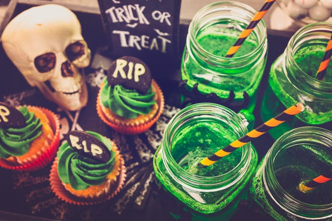 A collection of bright green Halloween drinks served with green iced gravestone cupcakes and a skull decoration