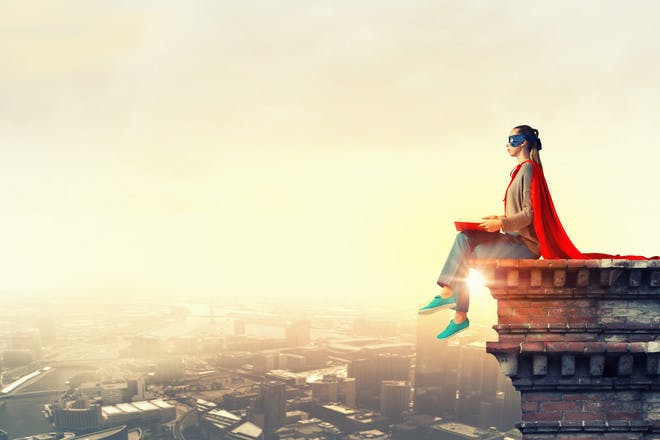 superwoman sitting on ledge looking over city