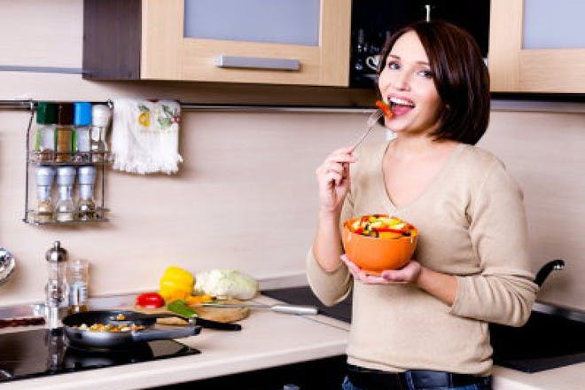 woman eating from bowl in kitchen