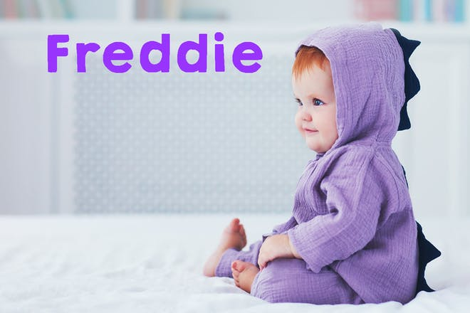 Baby with red hair in purple dinosaur costume. Text says Freddie