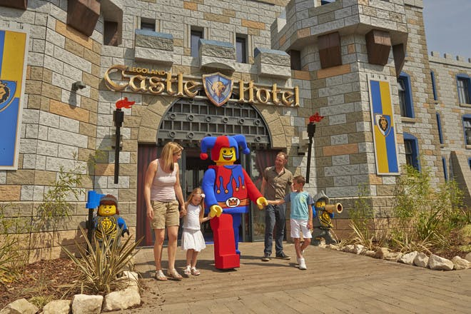 Family with Lego mascot in front of Castle Hotel at Legoland Windsor