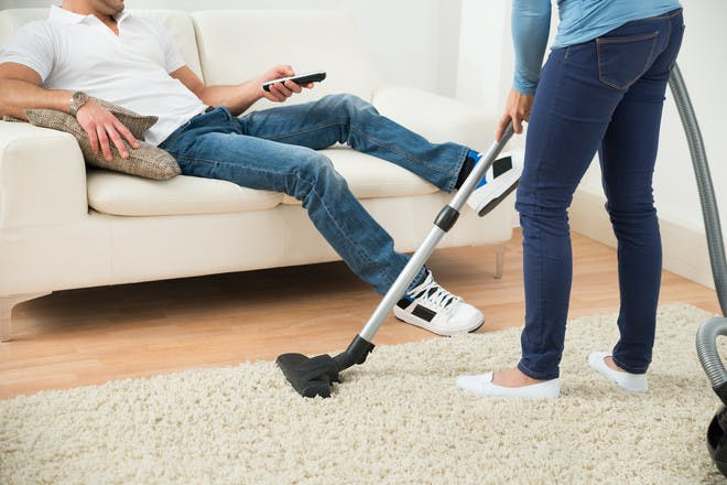 Woman hoovering while man sits on cough watching TV