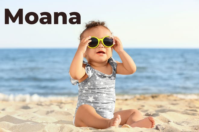 baby sat on beach with Moana written in text