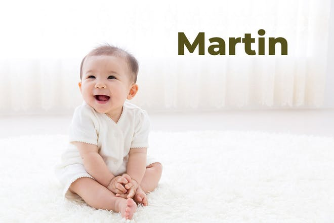 Baby sitting up and laughing. Name Martin written in text