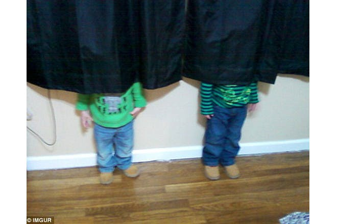 two children hiding behind curtain