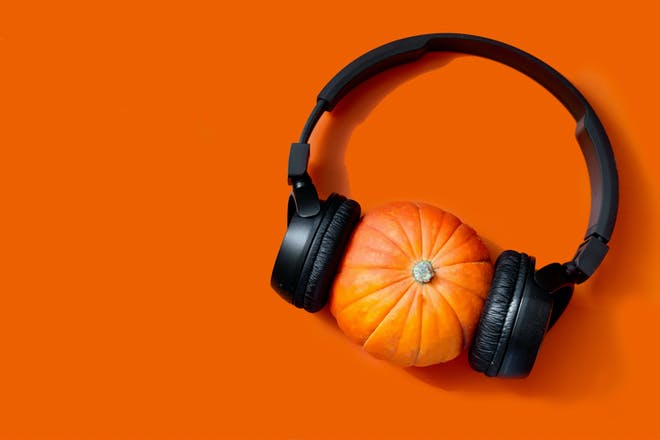 Pumpkin on an orange background with headphones