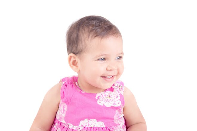 little girl happy wearing pink dress on white background