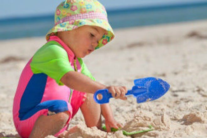 baby in bright costume playing with spade in sand at the beach