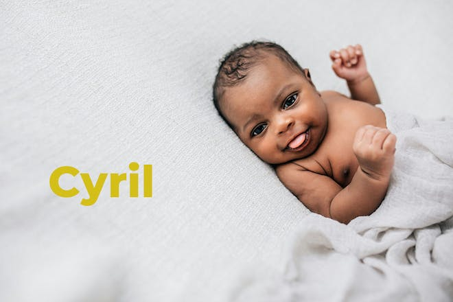 Baby lying down and sticking tongue out. Name Cyril written in text