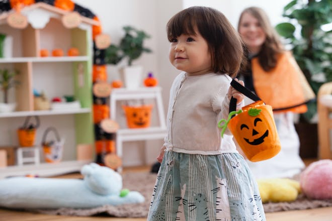 Toddler girl dancing at Halloween party while carrying an orange pumpkin bucket
