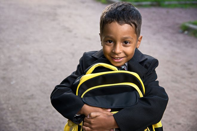 Young boy holding school bag and smiling