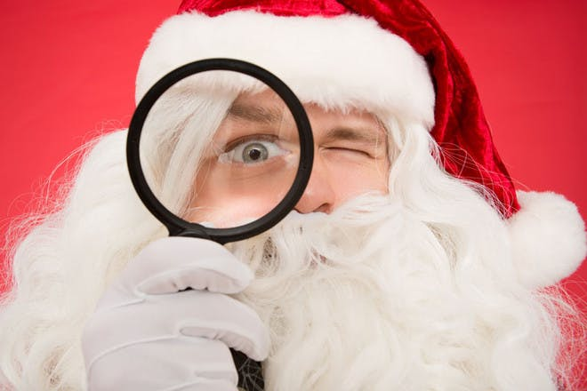 Santa is watching closely with a magnifying glass
