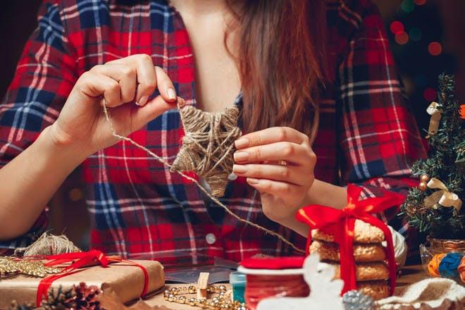 Woman making woven Christmas stars