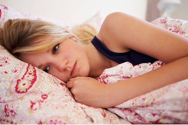 teen looking sad lying in bed
