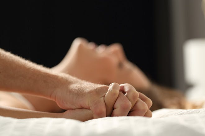 couple clenching hands on bed sex