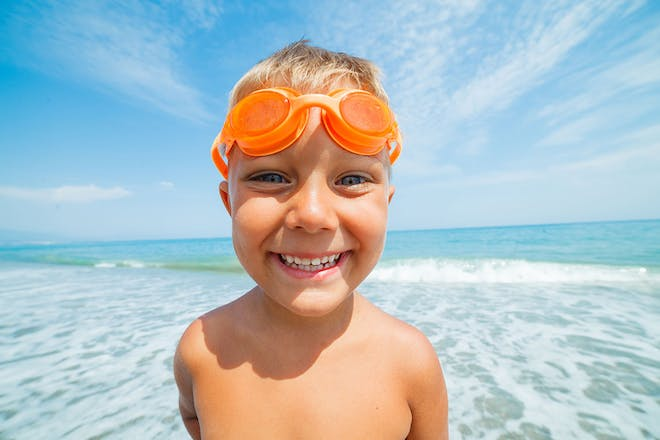 young boy with orange goggles standing in sea