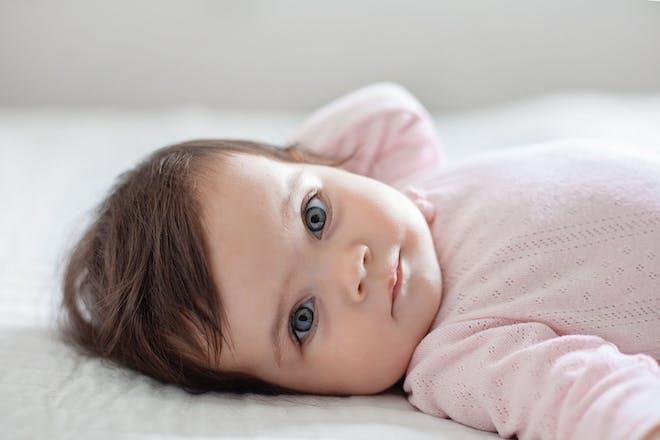 Baby lying down wearing pink babygro