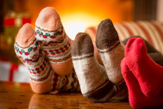 three pairs of feet wearing christmas socks