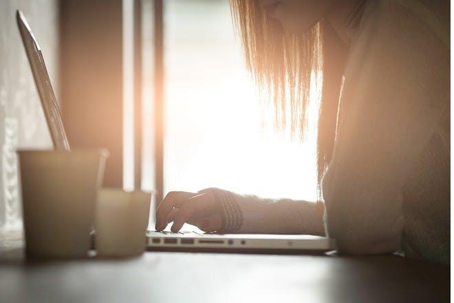 woman using laptop in sunlight
