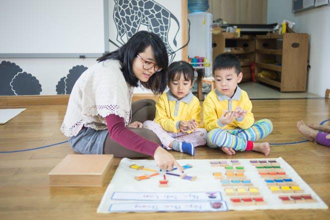 Woman teaching Montessori to two children
