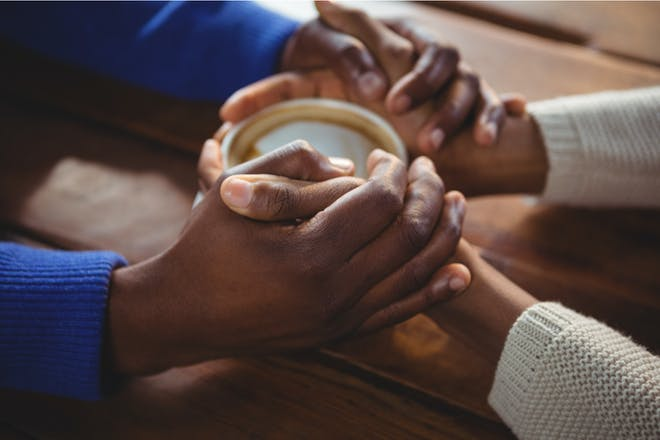 Couple holding hands over a coffee