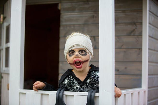 Toddler dressed in zombie costume with bandages wrapped round head and face paint on for Halloween party